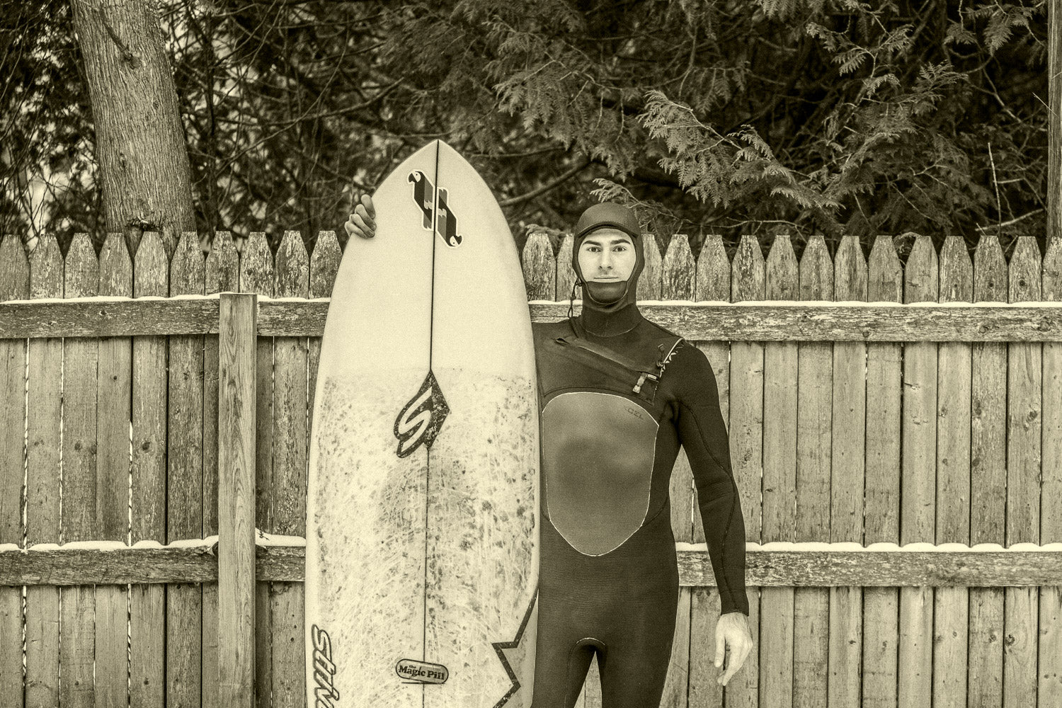 Surfer stands in hooded wetsuit next to surfboard. Behind runs an old fence with a dusting of snow.