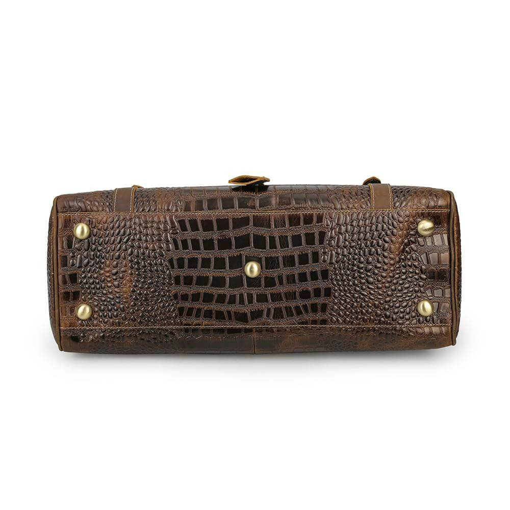 Luxury leather travel duffel bag has unique appearance from embossed crocodile design bottom view with five studs protecting the bottom