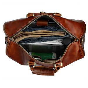 Royalties oil wax top grain genuine leather duffel bag interior with clothing, water bottle, and pair of sunglasses.