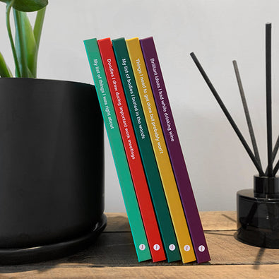 Five WTF Notebooks hardcovers with funny titles leaning against plant
