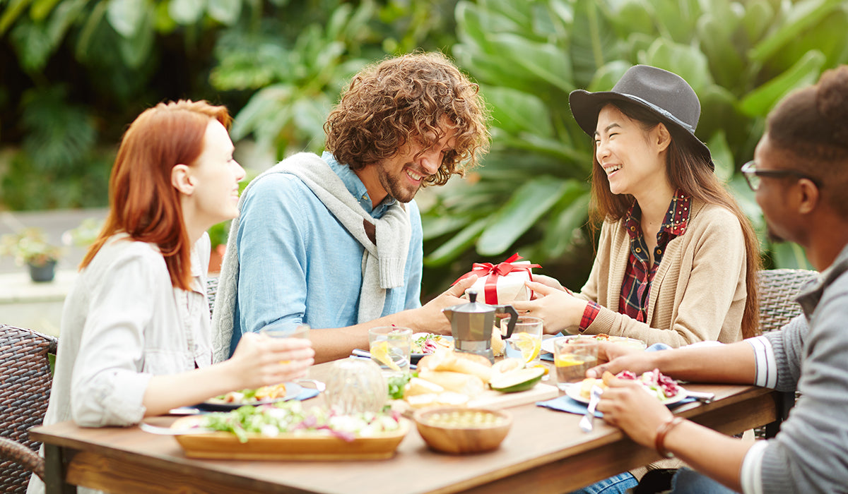 Four friends sitting at table celebrating with inappropriate gag gift