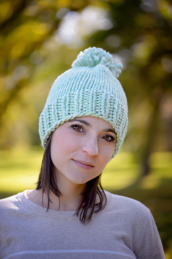 A young woman wearing our Snowball Fight Hat in the woods. Shown in Cucumber.
