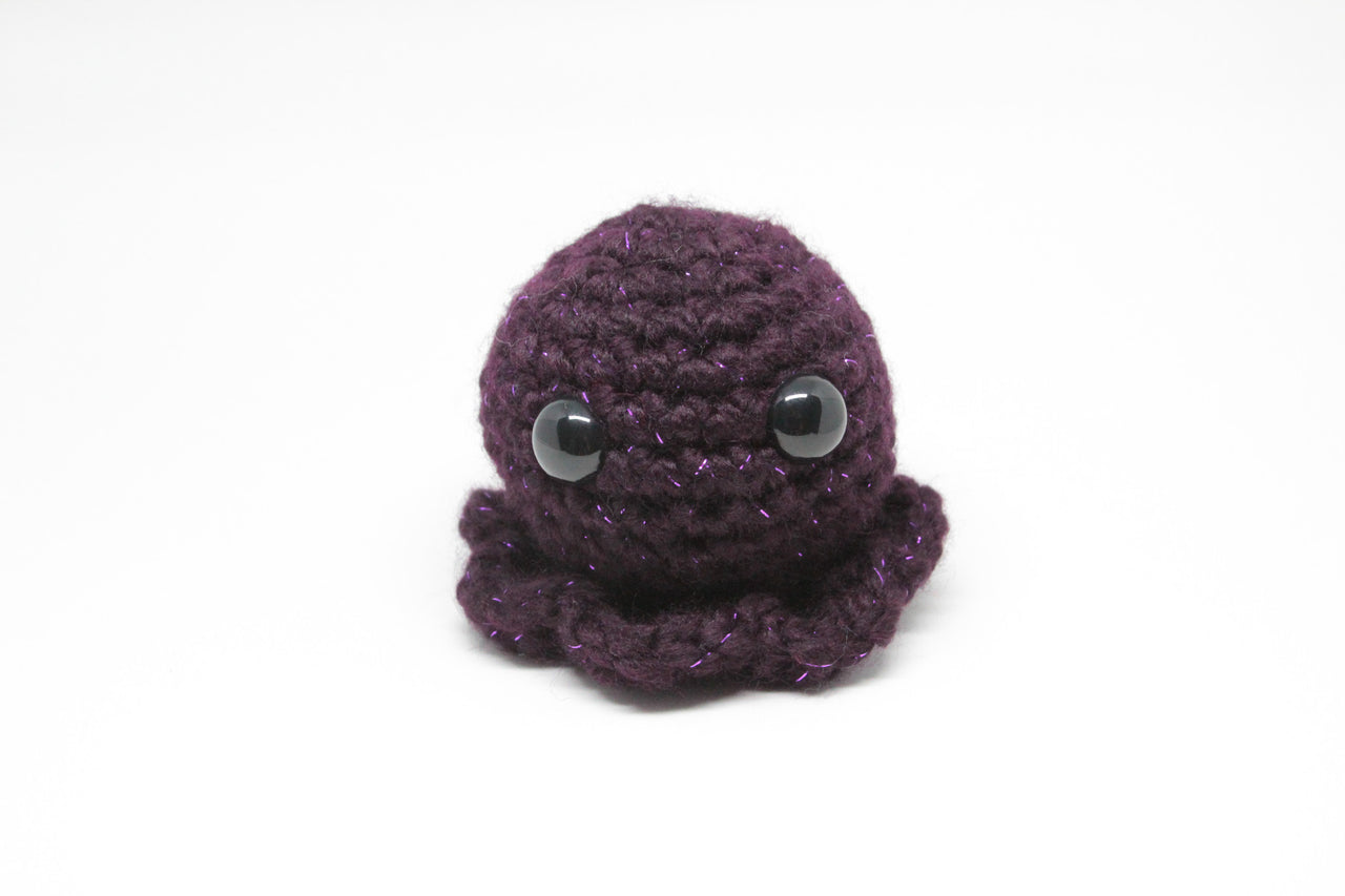 Our larger octopus made in a dark purple yarn with a sparkly thread running through it.