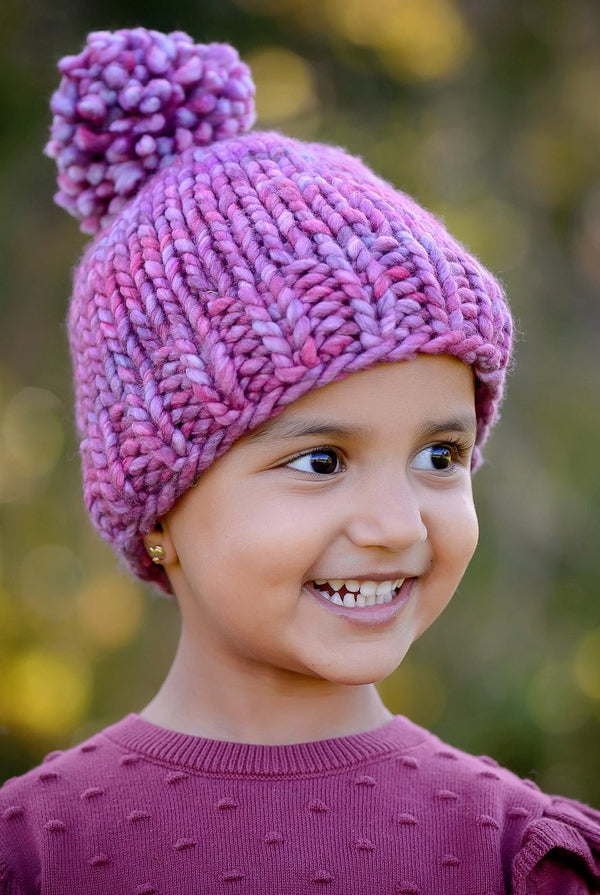 A little girl is shown wearing the Snowball Fight Hat. Shown in Porhinno.