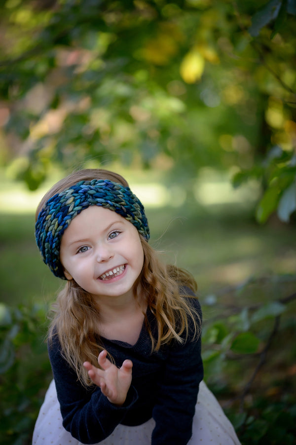A little girl reaches towards the camera while playing in the forest while wearing a Little Twist Headband. Shown in Verde Azul.