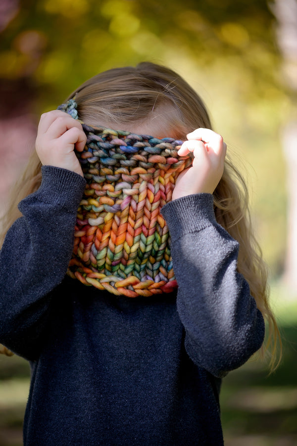 A small child pulling a cowl over her face in the woods. Shown in Arco Iris