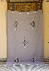 Embroidered Throw: Light Grey Throw with Stacked Diamond Patterns and White Pom Poms