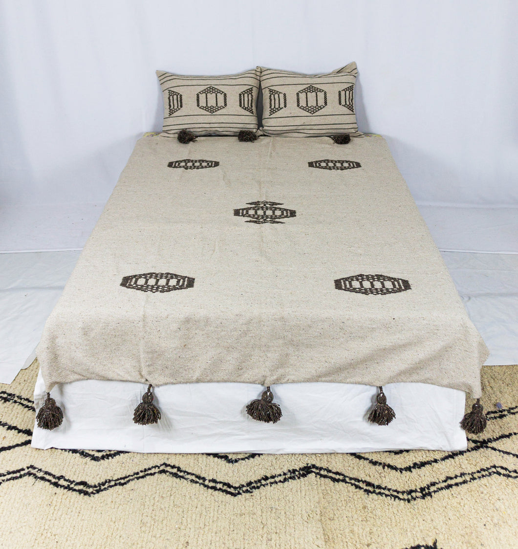 Embroidered Throw: Beige Throw with Brown Design and Brown Pom Poms