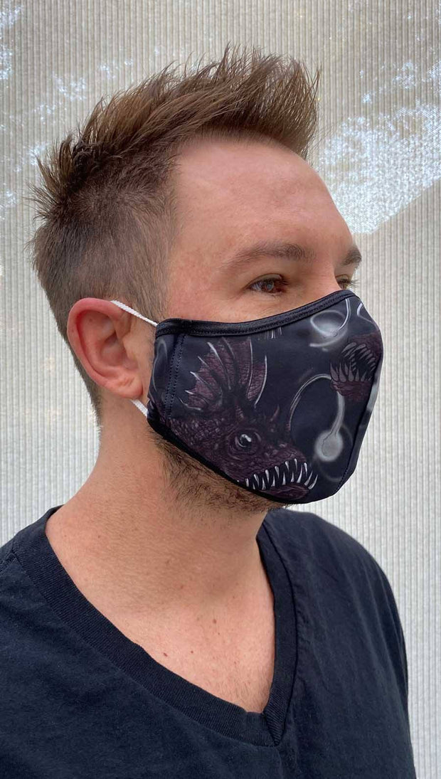 Right side view of male model wearing a black mask with two dark purple deep sea angler fishes