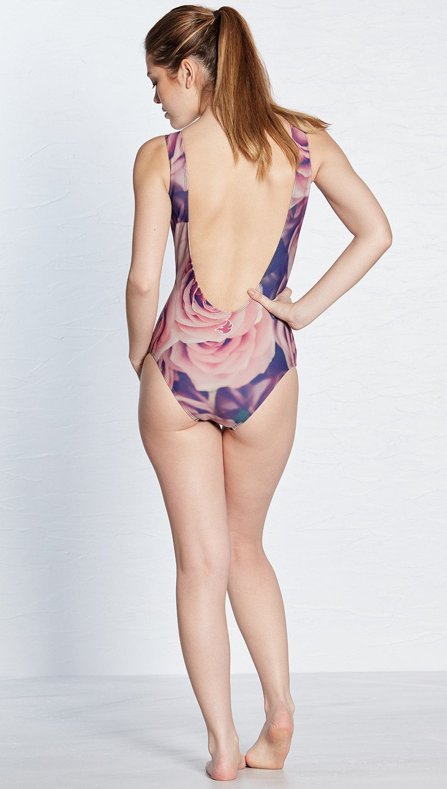 closeup front view of model wearing floral rose themed one piece swimsuit / leotard