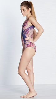 left side view of model wearing floral rose themed one piece swimsuit / leotard