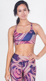 closeup front view of model wearing pink floral inspired printed sports bra and matching leggings