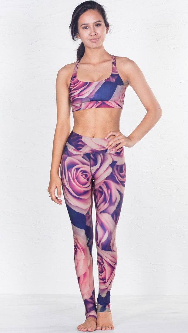 front view of model wearing pink floral inspired printed sports bra and matching leggings
