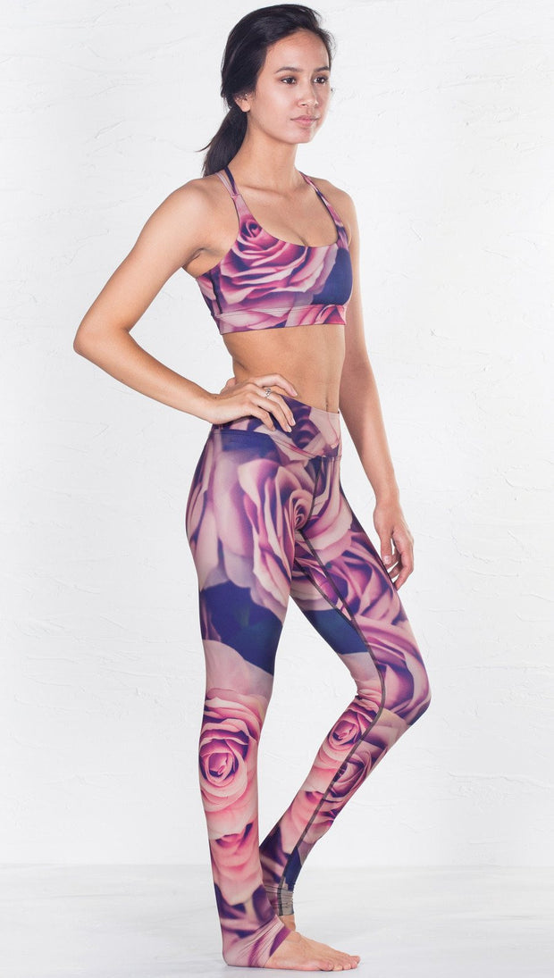 slightly turned front view of model wearing pink floral inspired printed sports bra and matching leggings
