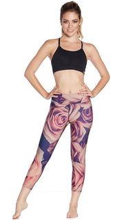 front view of model wearing printed capri leggings with all-over rose design motif and sports top