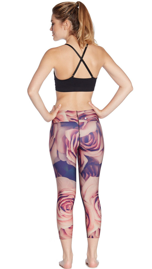 back view of model wearing printed capri leggings with all-over rose design motif and sports top