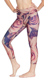 close up front view of model wearing printed capri leggings with all-over rose design motif