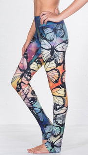 left side view of model wearing colorful butterfly themed printed full length triathlon leggings