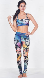 front view of model wearing colorful butterfly inspired printed sports bra and matching leggings