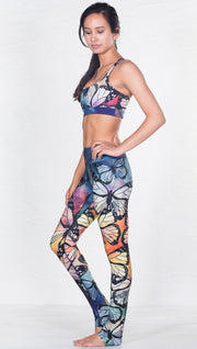 left side view of model wearing colorful butterfly inspired printed sports bra and matching leggings