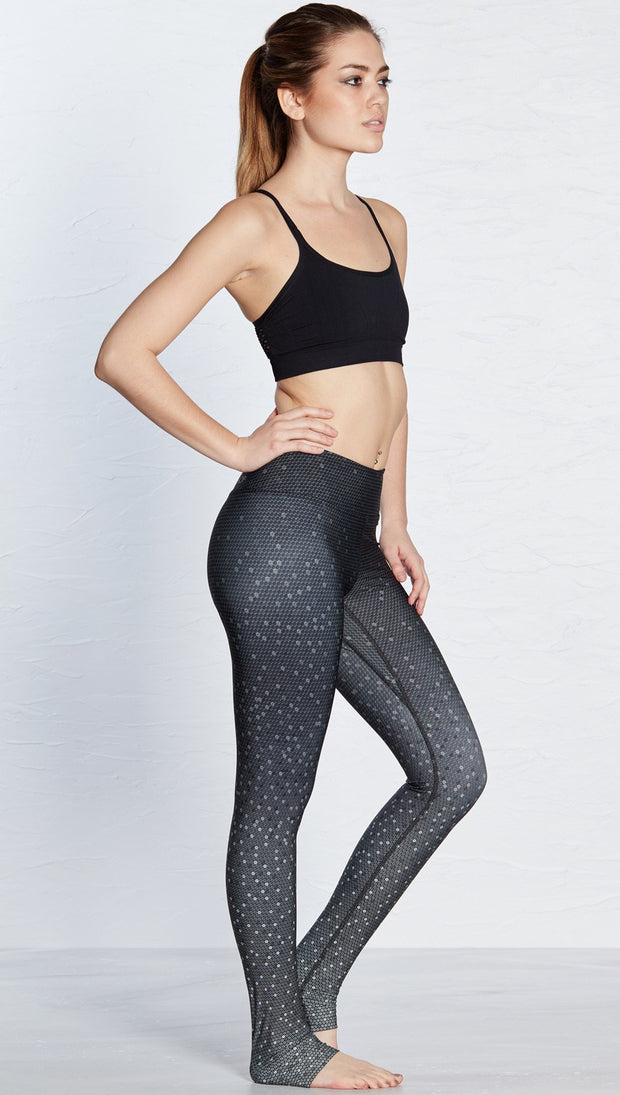 right side view of model wearing black ombre beaded printed full length leggings with black sports top
