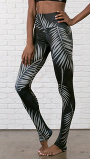 close up slightly turned front view of model wearing full length black leggings with white palm design