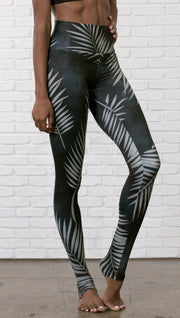 closeup slightly turned front view of model wearing full length black leggings with white palm design