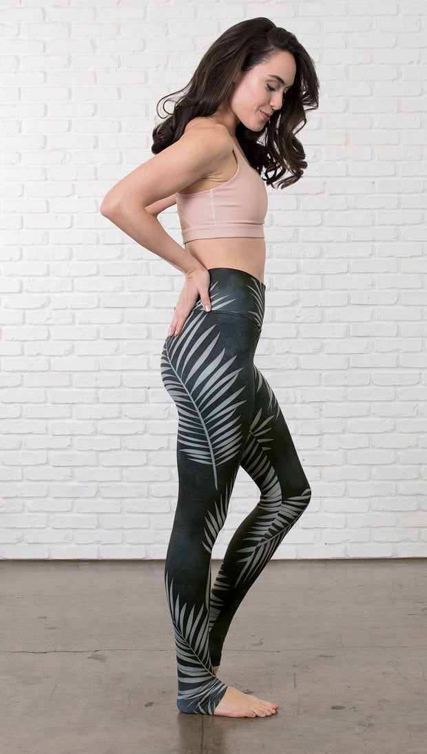 right side view of model wearing full length black leggings with white palm design and sports top