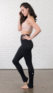 Left side view of model wearing black full-length leggings