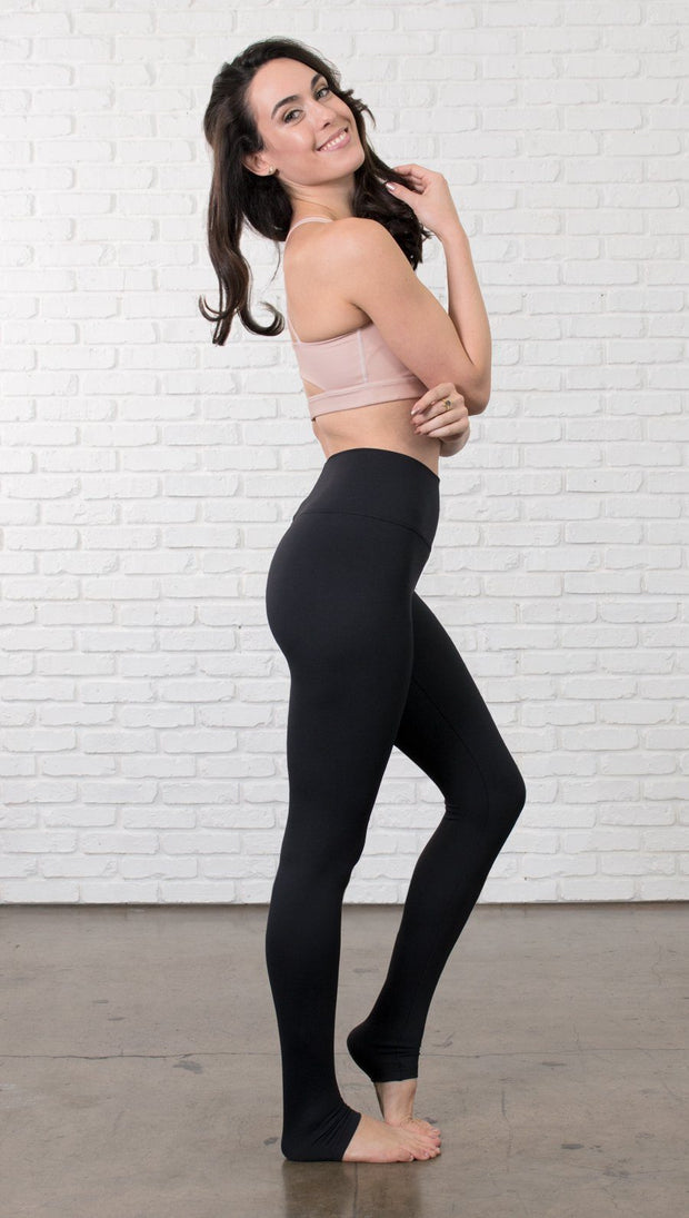 Right side view of model wearing black full-length leggings