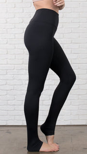Closeup right side view of model wearing black full-length leggings