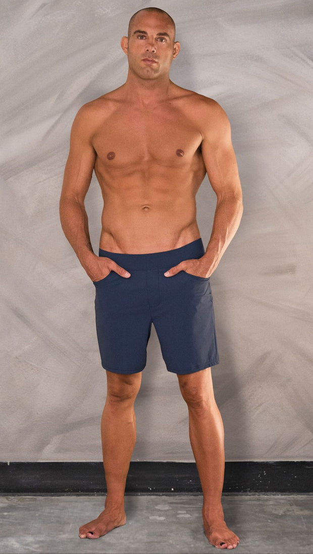Front view of model wearing men's blue performance shorts with slim fit.