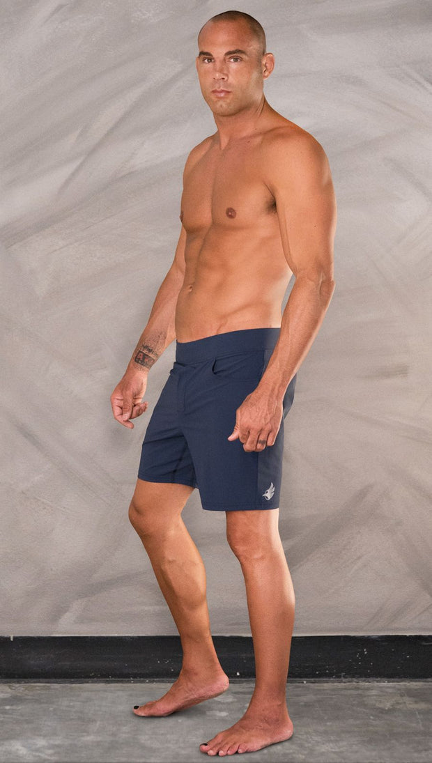 Left side view of model wearing men's blue performance shorts with slim fit.