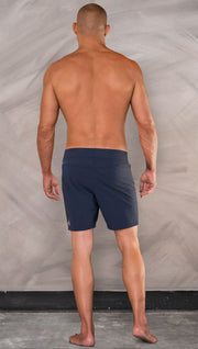 Back view of model wearing men's blue performance shorts with slim fit.