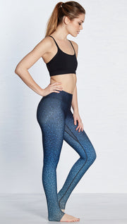 right side view of model wearing beaded blue ombre themed printed full length leggings and sports top