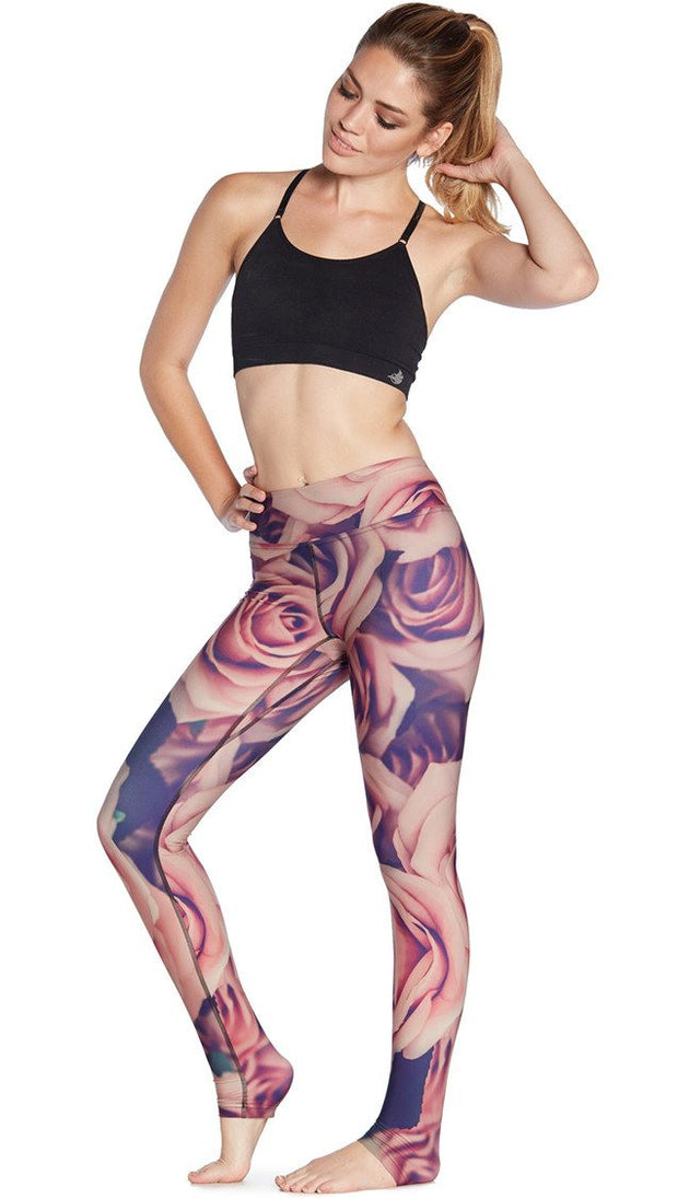 front view of model wearing printed full length leggings with all-over rose design motif and sports top