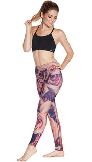 slightly turned front view of model wearing printed full length leggings with all-over rose design motif