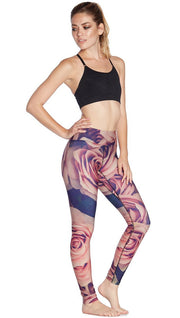 slightly turned front view of model wearing printed full length leggings with all-over rose design motif and sports top