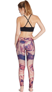 back view of model wearing printed full length leggings with all-over rose design motif and sports top