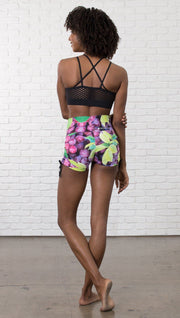 back view of model wearing athletic shorts with all over printed grapes and leaves design and sports top
