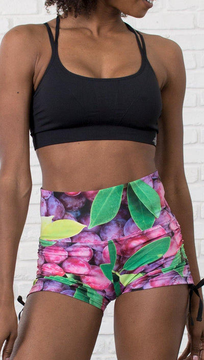 closeup view of model wearing athletic shorts with all over printed grapes and leaves design and sports top