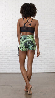 back view of model wearing athletic shorts with all over printed kale leaves design and sports top