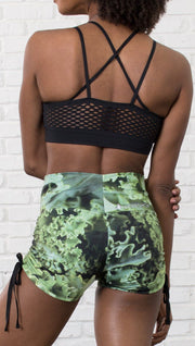 closeup back view of model wearing athletic shorts with all over printed kale leaves design and sports top