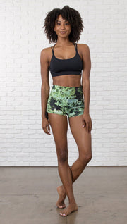 front view of model wearing athletic shorts with all over printed kale leaves design and sports top