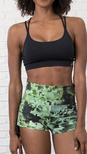 closeup view of model wearing athletic shorts with all over printed kale leaves design and sports top