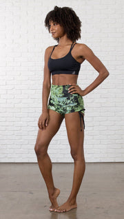 slightly turned front view of model wearing athletic shorts with all over printed kale leaves design and sports top