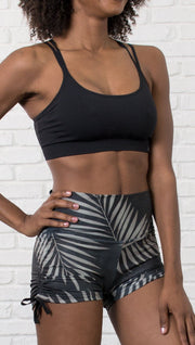 slightly turned closeup front view of model wearing black athletic shorts with printed white palm design and sports top