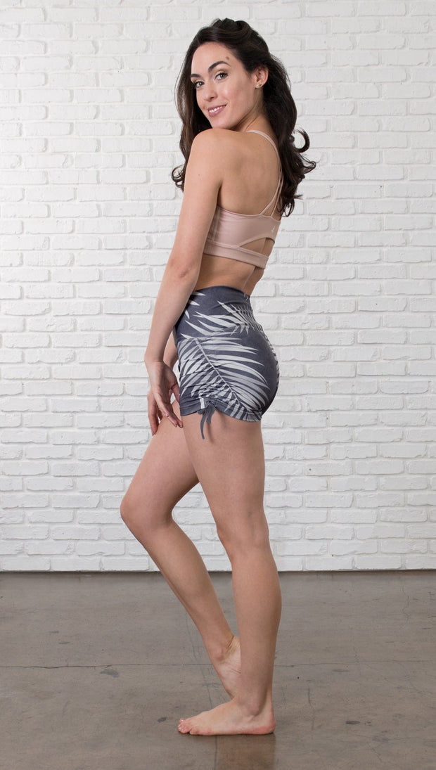 left side view of model wearing athletic shorts with all over printed palms design and sports top