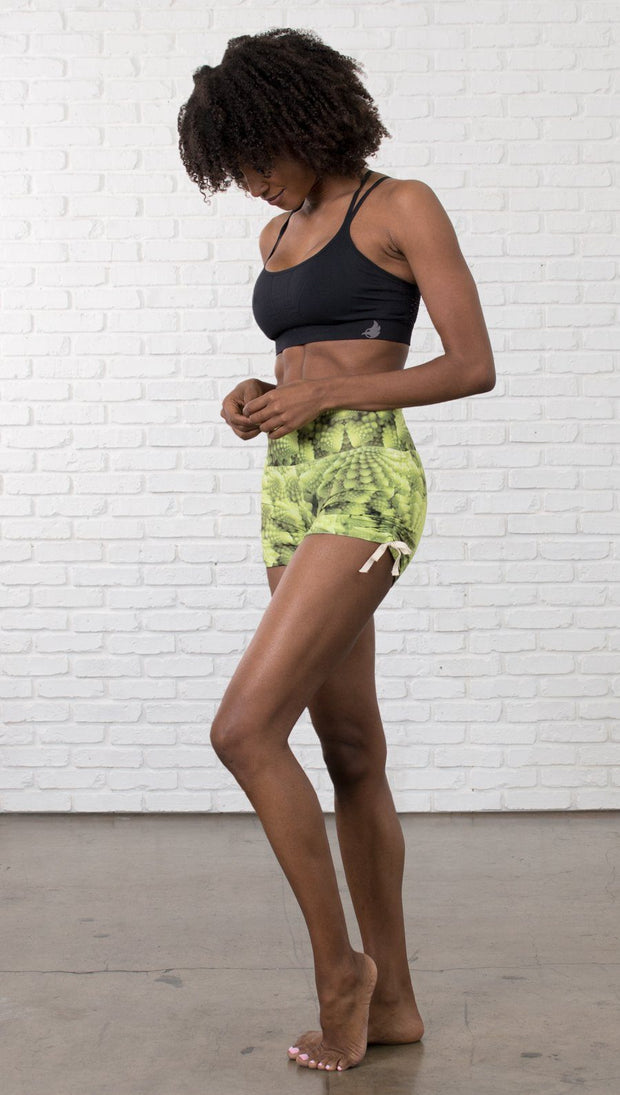 left side view of model wearing athletic shorts with all over printed romanesco broccoli design and sports top
