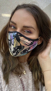 Slightly turned front view of model wearing a colorful butterfly themed mask